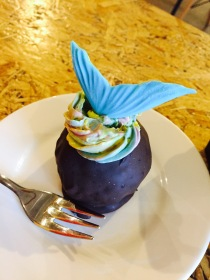A rainbow cake 'bomb' with a mermaid tail